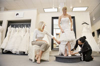 Mother watching as mature employee helping bride with footwear in bridal boutique