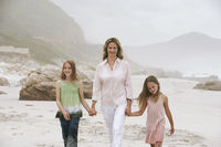 Mother with two daughters  7-9 10-12  walking on beach