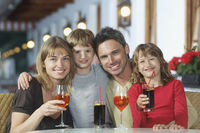 Parents and children  7-9  with drinks at restaurant portrait