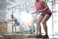 People doing box jump exercise in crossfit gym