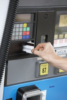 Person paying with credit card at gas pump close up of hand