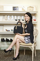 Portrait of a mid adult woman showing designer handbag in footwear store