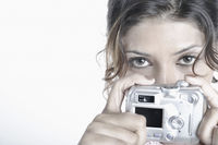 Portrait of a young woman holding a digital camera