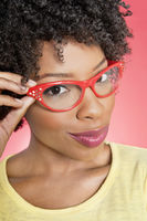 Portrait of an african american woman wearing retro glasses over colored background