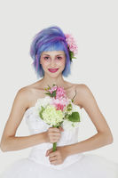 Portrait of beautiful young woman in wedding dress with dyed hair against gray background