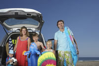 Portrait of family with three children  3-11  at beach by car