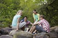 Popular : Portrait of four teenagers  16-17 years  sitting on stones by river smiling