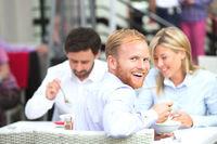 Portrait of happy businessman sitting with colleagues at outdoor restaurant