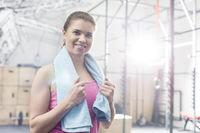 Popular : Portrait of happy woman holding towel around neck in crossfit gym