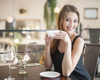 Portrait of happy young woman having coffee at restaurant