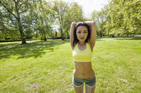 Portrait of young fit woman stretching at park