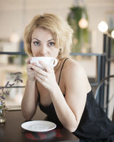 Portrait of young woman having coffee at restaurant table