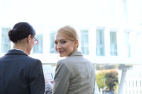 Rear view of portrait of smiling businesswoman sitting with colleague outdoors
