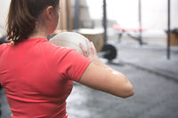 Popular : Rear view of woman holding medicine ball in crossfit gym