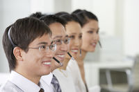 Row of customer service representatives wearing telephone headsets in office head and shoulders