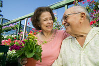 Senior couple sitting among flowers at plant nursery close up
