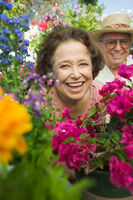Senior couple sitting in plant nursery seen through bed of flowers portrait