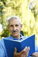 Popular : Senior man holding a book while looking at the camera