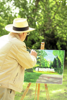 Senior man painting in the park