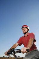 Popular : Senior man with safety helmet riding on a bicycle