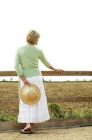 Popular : Senior woman holding a hat on her back