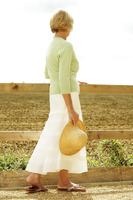 Popular : Senior woman holding a hat while taking a stroll