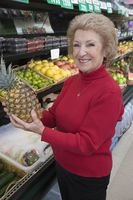 Senior woman holding pineapple in supermarket