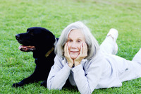 Senior woman lying on the field with her dog
