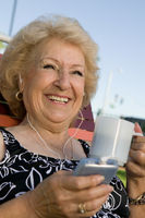 Senior woman outdoors listening to portable music player holding cup smiling