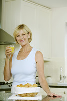 Senior woman smiling while holding a glass of orange juice