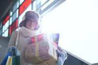 Smiling woman with stacked gifts and shopping standing by window during winter