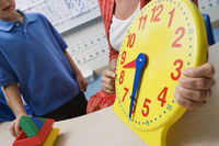 Teacher demonstrating time to children