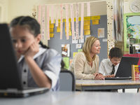 Teacher sitting with student using laptop in classroom