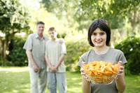 Teenage girl holding a bowl of chips with her brother and father standing in the background