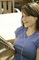 Teenage girl listening to music while reading book