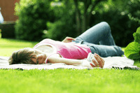 Teenage girl lying on the field listening to music on a portable mp3 player