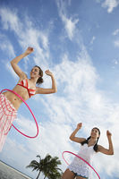 Teenage girls  16-17  playing with hoola hoop on beach low angle view