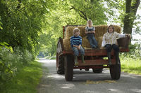 Three children  5-9  sitting on trailer on country lane
