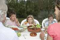 Three-generation family with three children  6-11  sitting at table in garden