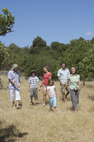 Three-generation family with two children  6-11  walking in field