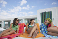 Popular : Three teenage girls  16-17  lying on sunloungers