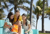 Popular : Three teenage girls  16-17  sitting in park looking at shopping bags