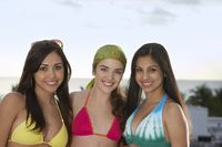 Popular : Three teenage girls  16-17  wearing bikinis portrait