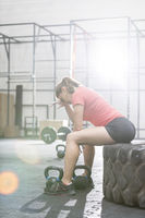 Popular : Tired woman sitting on tire in crossfit gym