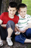 Two boys sharing a portable mp3 player