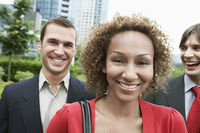 Two business men and woman smiling outdoors portrait