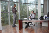 Two business men talking at desk in office