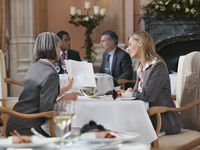 Two business women looking at documents at restaurant table men in background