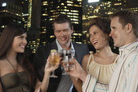 Two elegant couples toasting against city night skyline