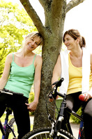 Two women smiling while sitting on bicycles